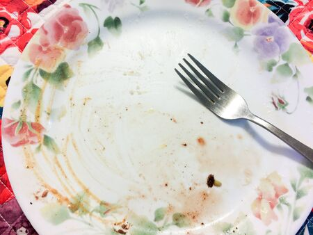 Empty dinner plate dirty with fork after yummy saisfying meal