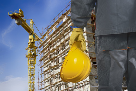 worker with helmet in front of construction scaffolding and construction crane