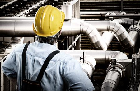 Foto de Worker in protective uniform and protective helmet in front of industrial pipes - Imagen libre de derechos