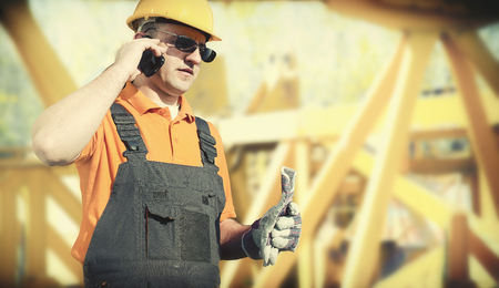 worker in protective uniform and protective helmet in front of construction crane - toned image, retro film filtered in instagram style