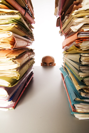 Foto de Man with bald head peaks above desk to see stacks of files and folders waiting for his attention. - Imagen libre de derechos
