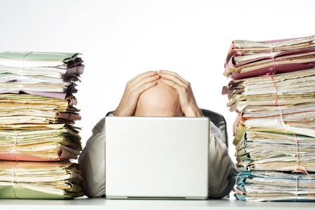 Foto de Male businessman sitting behind a laptop, his face hidden, with his hands on top of his head.  Two large piles of paperwork are piled on each side of the model, towering over his head.  Isolated on white background. - Imagen libre de derechos