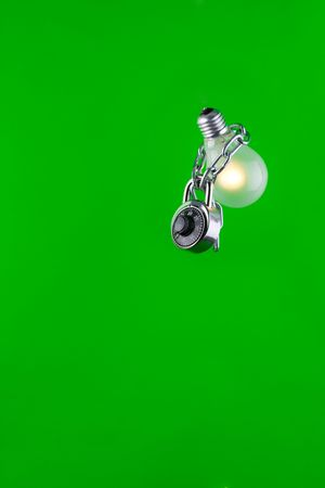 Light-bulb safely locked with a metallic chain, isolated on a green background.