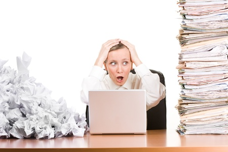A woman sitting at her desk with papers stacked up.