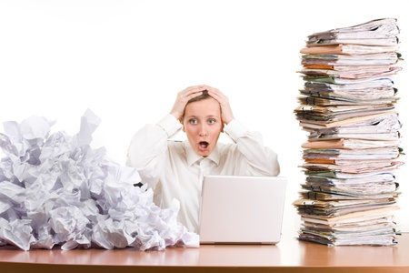 Photo pour A young woman stressed at work with a pile of paperwork.  - image libre de droit