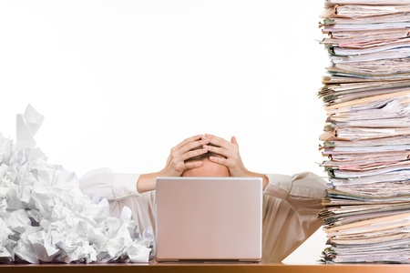 A stressed person holding his head behind a laptop surrounded by a pile of files and papers,