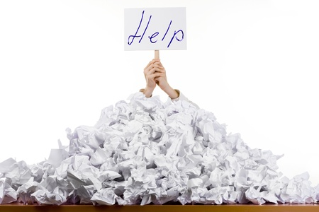 Foto de Person under crumpled pile of papers with hand holding a help sign isolated against a white background. - Imagen libre de derechos