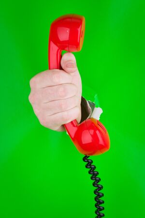 A view of a human hand holding a red telephone handset against a bright green background.
