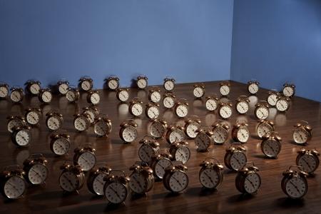 Many alarm clocks on a wooden floor. Art installation.