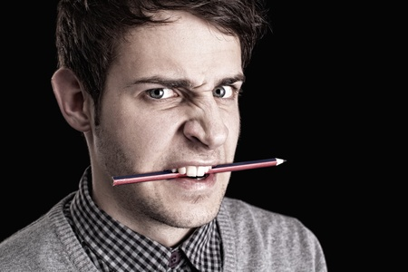 portrait of a young angry man with pencil