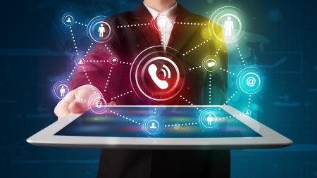 Foto de Young businessman showing social networking technology with colorful lights - Imagen libre de derechos