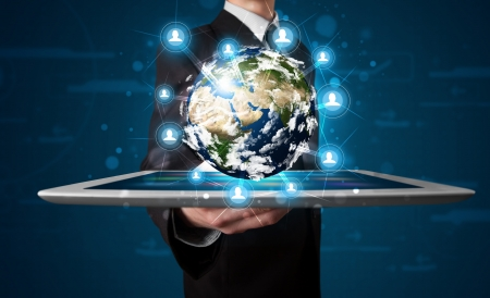 Young businessman presenting 3d earth globe in tabletの写真素材