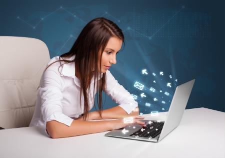 Pretty young lady sitting at dest and typing on laptop with message icons comming out
