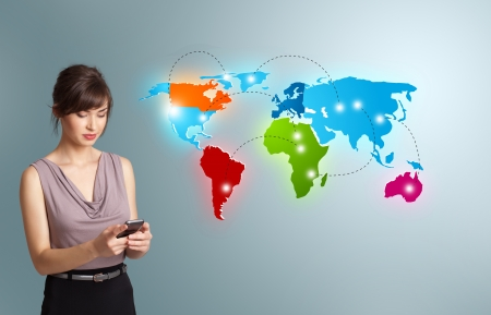 Beautiful young woman holding a phone and presenting colorful world map