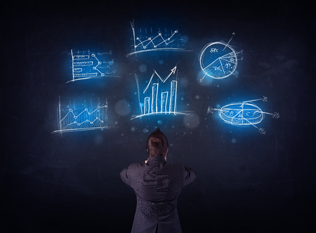 Young businessman standing in front of glowing charts and diagrams