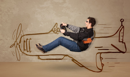 Funny pilot driving a hand drawn airplane on the wall concept