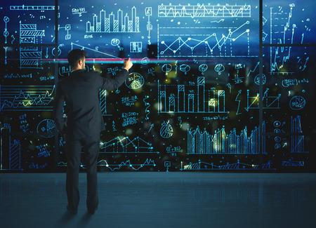 Photo pour Businessman drawing business statistics on glass wall - image libre de droit