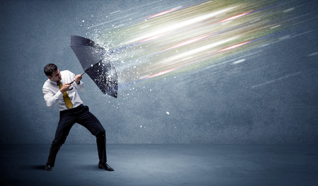 Foto de Business man defending light beams with umbrella concept on background - Imagen libre de derechos