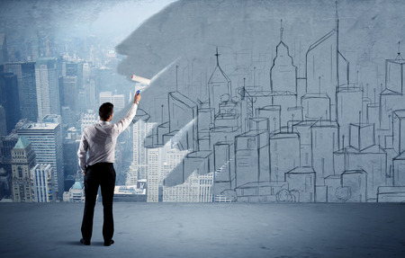Foto per A businessman in elegant suit holding a paint roller in his hand and painting drawn city landscape over urban skyscrapers concept - Immagine Royalty Free