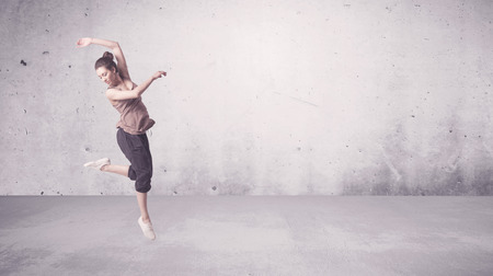 Photo for A beautiful young hip hop dancer dancing contemporary urban street dance in empty clear grey wall background concept. - Royalty Free Image