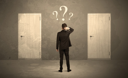 Foto de Salesman standing in front of two doors, unable to make the right decision concept with question marks above his head - Imagen libre de derechos