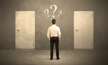 Photo pour Salesman standing in front of two doors, unable to make the right decision concept with question marks above his head - image libre de droit