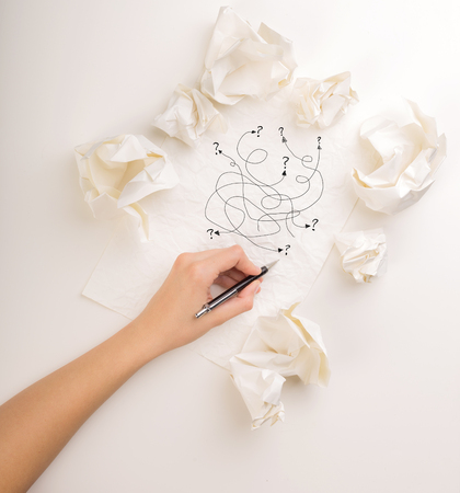 Female hand next to a few crumpled paper balls drawing random scribbles