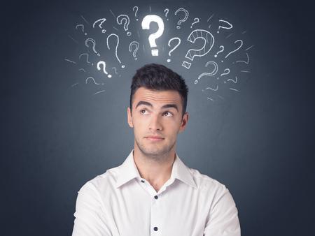 Photo pour Young casual businessman with white question marks above his head - image libre de droit