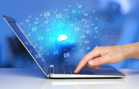 Hand using laptop with centralized cloud computing system concep