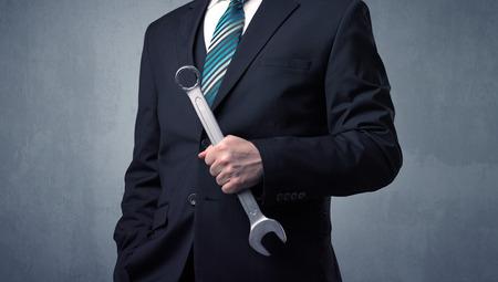 Photo pour Businesman standing with tool on his hand - image libre de droit