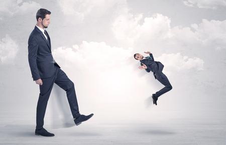 Big boss kicking little employee