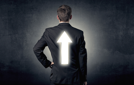 Young businessman standing with arrow on his back
