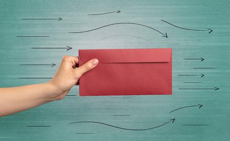 Photo pour Hand holding envelope with arrows around - image libre de droit
