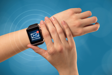 Hand with smartwatch and blue background