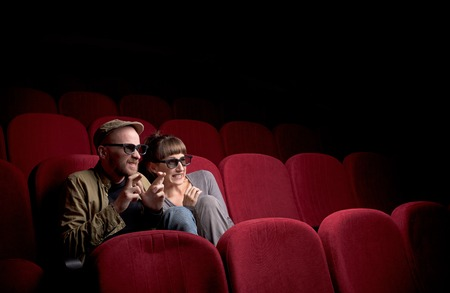 Photo pour Young couple sitting at red movie theatre - image libre de droit
