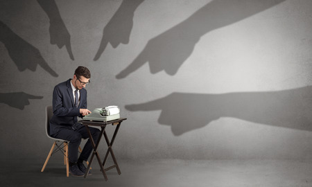 Photo pour Shadow hands pointing at a small worker - image libre de droit