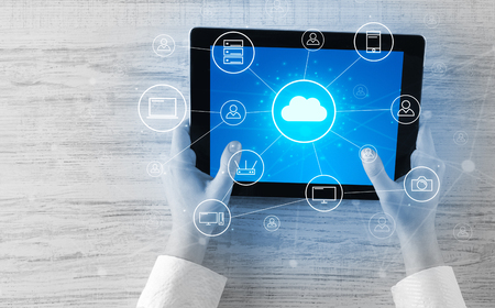 Foto de Hand using tablet with centralized cloud computing system concept - Imagen libre de derechos