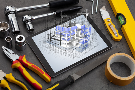 Photo pour Tablet with construction tools and 3d house plan concept - image libre de droit