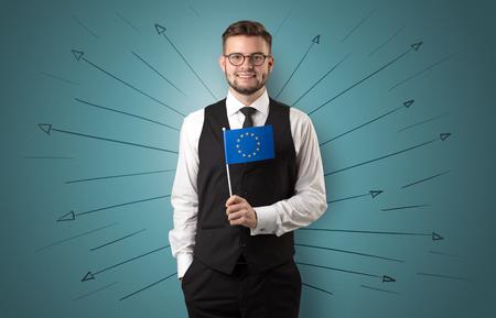 Foto de Smiling young man standing with flag and multidirectional arrows around - Imagen libre de derechos