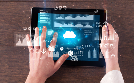 Hand holding tablet and checking finantial report on cloud computing system