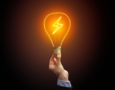 Photo for Hand holding light bulb on dark background. New Eco idea concept - Royalty Free Image