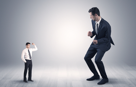 Photo for Big debutant young businessman scared of small strong businessman - Royalty Free Image
