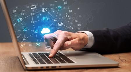 Photo pour Businessman hand sending a bunch of messages on laptop with cloud computing concept - image libre de droit