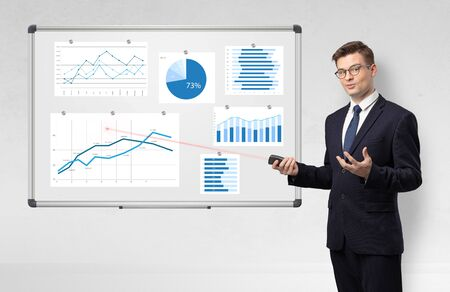 Photo pour Handsome businessman presenting report on white board with laser pointer - image libre de droit