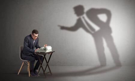 Photo pour Little man working and a big shadow arguing with him - image libre de droit