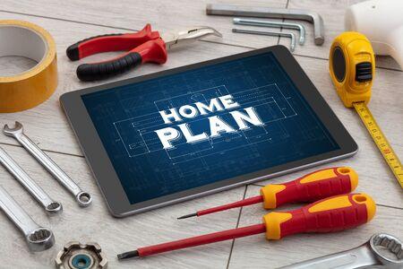 Photo pour Tablet and tools with home under construction concept  - image libre de droit