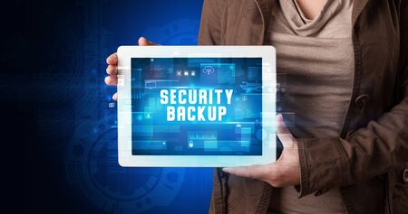 Photo pour Young business person working on tablet and shows the digital sign: SECURITY BACKUP - image libre de droit