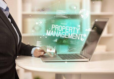Photo pour Side view of a business person working on laptop with PROPERTY MANAGEMENT inscription, modern business concept - image libre de droit
