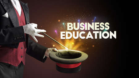 Illusionist is showing magic trick with BUSINESS EDUCATION inscription, new business model concept