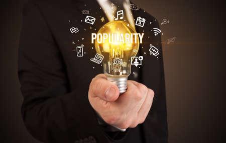 Photo pour Businessman holding light bulb with POPULARITY inscription, social media concept - image libre de droit